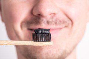 Lächelnder Mann hält eine Zahnbürste mit Aktivkohle-Zahnpasta darauf