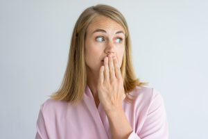 Portrait of shocked young Caucasian woman wearing pink blouse covering mouth with hand. Fear, bad breath concept