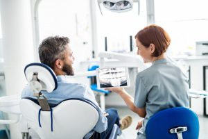 A rear view of man and dentist in dental surgery, annual check-up.
