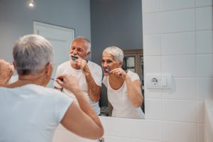 A happy senior couple having fun while brushing teeth on their morning routine.