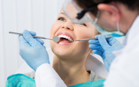 Regelmäßiger Zahnarztbesuch. Karies heilen. Junge Frau beim Zahnarzt