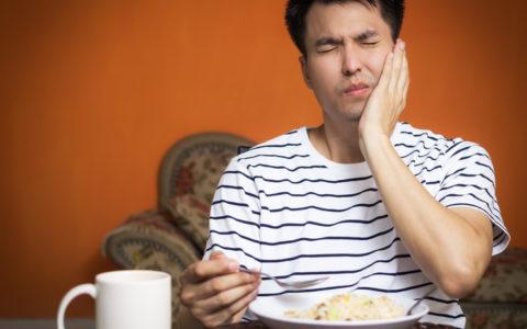 Mann hat überempfindliche Zähne und Zahnschmerzen beim Essen.