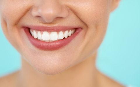 Schönes Lächeln mit weißen Zähnen. Nahaufnahme eines lächelnden Frauenmundes mit natürlich prallen, vollen Lippen und einem gesunden, perfekten Lächeln. Konzepte für Zahnaufhellung, Zahngesundheit und Lippenpflege.