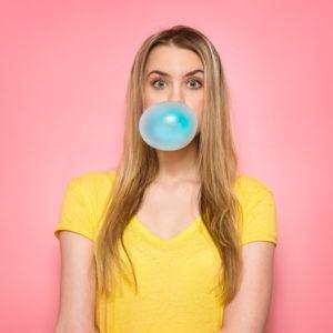 Frau vor pinkem Hintergrund macht eine Blase mit einem Kaugummi.