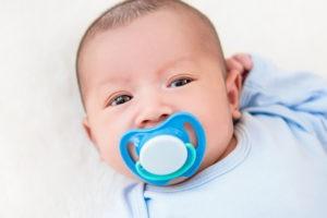 Baby mit blauem Schnuller.