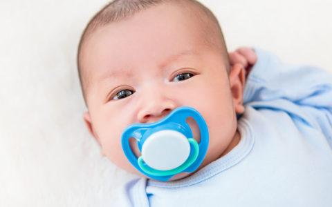 Bezauberndes kleines Neugeborenes mit Schnuller auf weißem Bettlaken liegend - Draufsicht