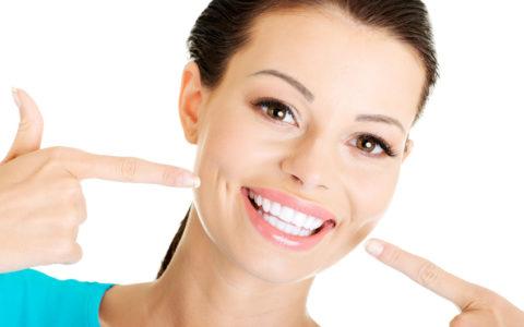 Frau, die ihre perfekten geraden weißen Zähne zeigt.