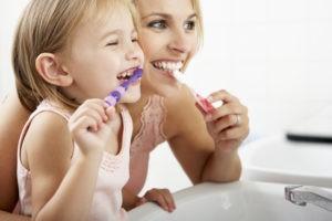 Mutter und Tochter putzen zusammen Zähne.