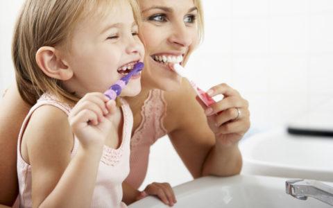 Mutter und Tochter putzen gemeinsam die Zähne