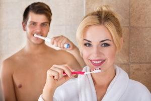 Mann und Frau, die sich die Zähne putzen.