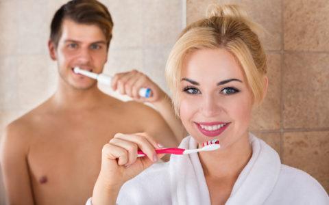 Porträt von Mann und Frau beim Zähneputzen im heimischen Badezimmer