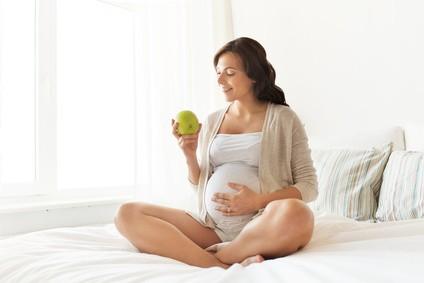 Konzept Schwangerschaft, gesunde Ernährung und Menschen - glückliche schwangere Frau isst zu Hause grünen Apfel
