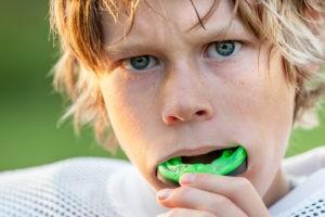 Junger Sportler, der einen Mundschutz trägt.