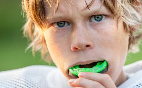 Junge setzt seinen Mundschutz ein