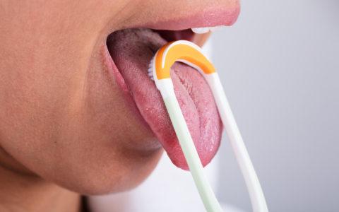 Foto einer jungen Frau, die ihre Zunge mit Reinigungsmittel reinigt