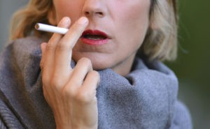 Frau mit rotem Lippenstift, die eine Zigarette raucht.