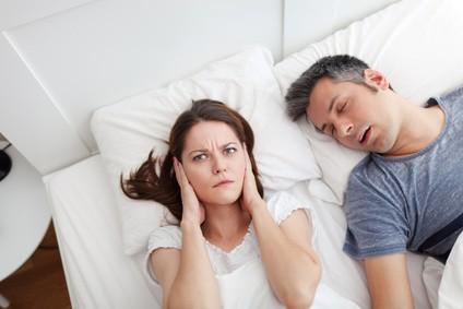 Frau hält sich die Ohren zu und ärgert sich über das Schnarchen ihres Mannes