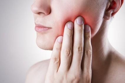 Frau mit Zahnschmerzen. Schmerz im menschlichen Körper auf grauem Hintergrund mit rotem Punkt
