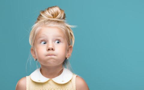 Kleines, junges, lustiges Mädchen, aufgeblasene Wangen auf blauem Hintergrund