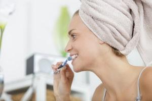 Frau, die sich die Zähne putzt.