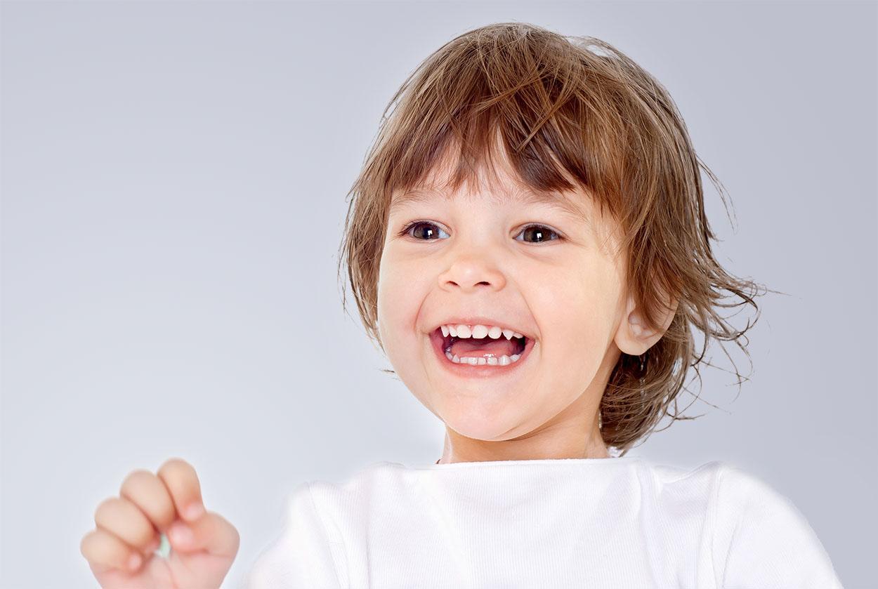 Lächelndes Kind vor einem grauen Hintergrund