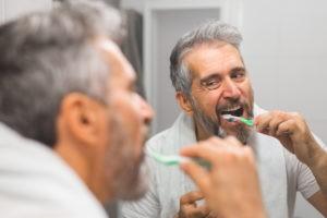 Älterer Mann, der sich vor dem Spiegel die Zähne putzt.