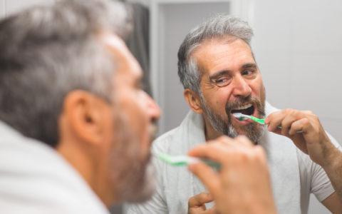 Grauhaariger Mann mittleren Alters mit Bart und grauem Haar beim Zähneputzen im Badezimmer
