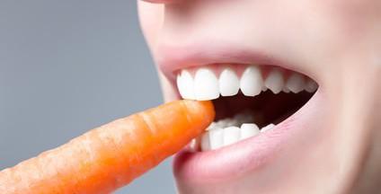 Nahaufnahme, Mann mit weißen Zähnen beißt in Karotte