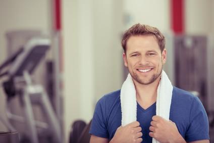 Mann im Fitnessstudio, der ein Handtuch um den Hals trägt