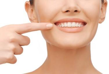 Zahngesundheitskonzept - schöne Frau zeigt auf ihre Zähne
