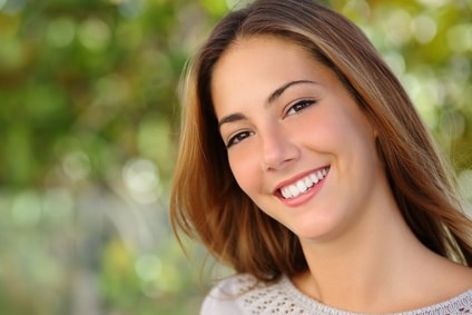 Lächelnde Frau mit weißen Zähnen vor verschwommenem Hintergrund