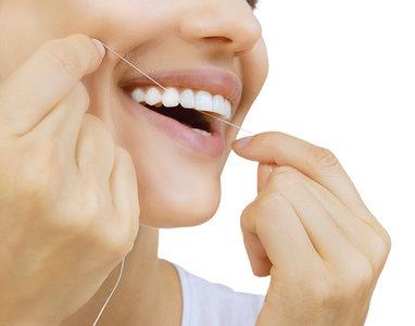 Frau und Zahnseide - Junge Frau benutzt Zahnseide (Nahaufnahme: Lächeln einer Frau)
