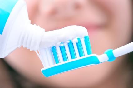 Nahaufnahme, Zahnpasta wird auf Zahnbürste geschmiert