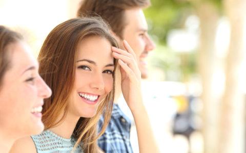 Frau mit weißem Lächeln und Zähnen zwischen Freunden auf der Straße