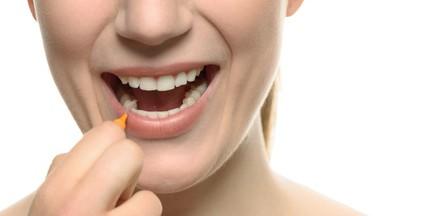 Frau, die ihre Zahnzwischenräume reinigt
