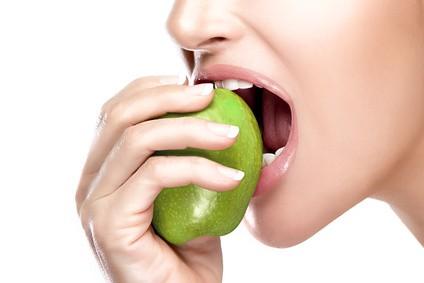 Nahaufnahme eines schönen gesunden Mundes, der in einen saftigen und sauren grünen Apfel beißt. Nahaufnahme eines isolierten Porträts auf weißem Hintergrund
