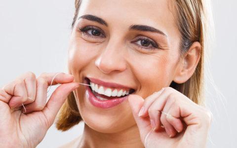 Lächelnde Frau benutzt Zahnseide