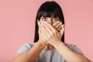 Frau, die sich den Mund vor pinkem Hintergrund zuhält.