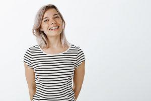 Frau, die vor grauem Hintergrund mit Zahnspange lächelt.