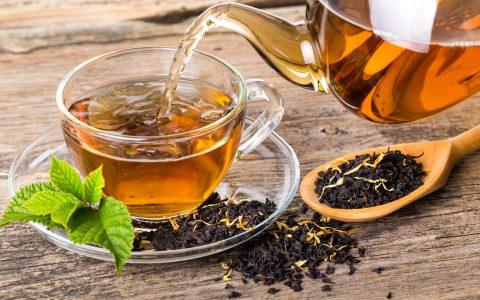 Tee wird in eine Tasse aus Glas gegossen
