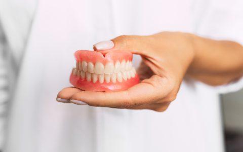 Zahnprothese, wird in einer Hand gehalten