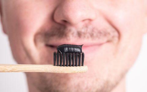 ein Mann putzt sich die Zähne mit einer schwarzen, bleichenden Zahnpasta unter Zusatz von Kohle, einer ökologischen Zahnbürste aus Bambus.