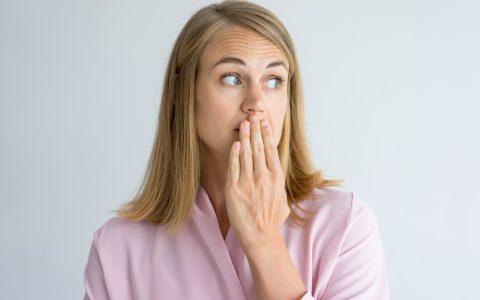 Porträt einer schockierten jungen kaukasischen Frau, die eine rosa Bluse trägt und den Mund mit der Hand bedeckt. Konzept Angst, Mundgeruch