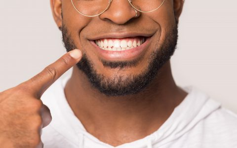 Close up of happy african American man isolated on grey studio background show point at white teeth, excited biracial male demonstrate wide healthy smile after good service dental treatment