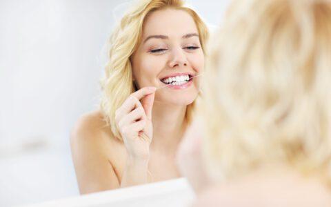 Blonde Frau steht vor Spiegel und verwendet Zahnseide