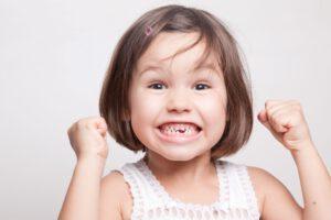 Kleines Mädchen mit Zahnlücke, das sich freut