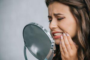 Nahaufnahme einer jungen Frau, die Zahnschmerzen hat und in den Spiegel schaut