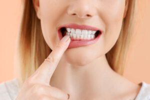 Lächelnde Frau mit weißen Zähnen vor farbigem Hintergrund, Nahaufnahme