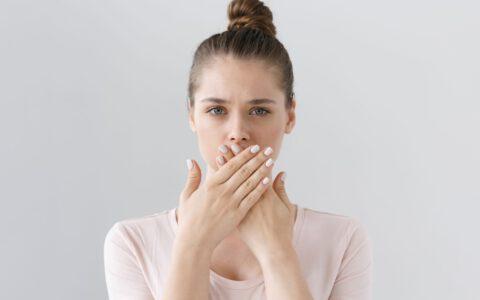 Junge Frau hält sich mit ihren Händen den Mund zu