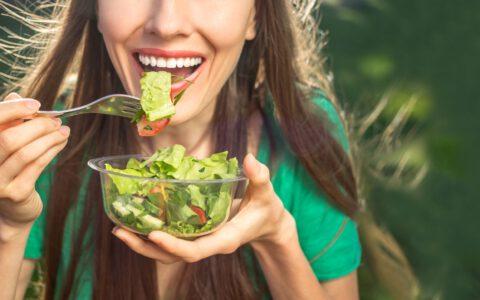 Eine Frau mit weißen Zähnen isst einen Salat